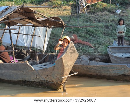 KOMPONG PHLUK, CAMBODIA - JANUARY 28 Some unidentified children greet tourists from a boat in the floating village of Kompong Phluk on January 28, 2016 in Kompong Phluk, Cambodia - stock photo