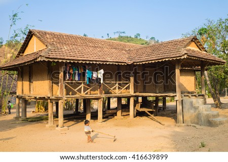 Kon Tum, Vietnam - Mar 28, 2016: Traditional typical Bahnar house in old minority village Kon Kotu, the most frequently visited of Bahnar villages in Kon Tum. A child playing on yard