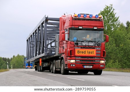 KONGINKANGAS, FINLAND - JUNE 20, 2015: Scania 164L 580 truck hauls a wide load. The abnormal transport permit is required, if any dimension of the transport exceeds the free dimension limits. - stock photo