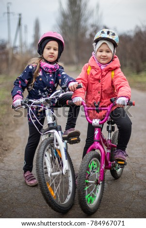KONSTANTINOVKA, UKRAINE - DECEMBER 30, 2017: Tw little girls on the street in the helmets with bicycles