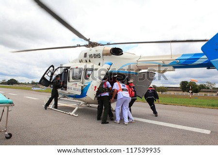 KORAT, THAILAND - SEP 15 : Bangkok Hospital Rescue team(white) pulling cart with wounded person to helicopter in Search and Rescue Exercise(SAREX) on September 15, 2012 in Nakhonratchasima,Thailand - stock photo