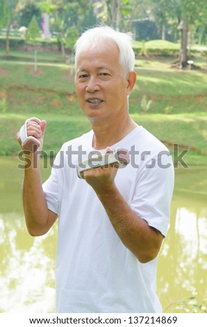 Korean Asian senior man healthy lifestyle working out on a park with a dumbbell - stock photo