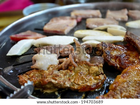 Korean barbecue - meat are being cooked on stove. - stock photo