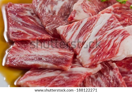 korean cuisine, freshness seasoned karubi beef on white dish with lettuce  - stock photo