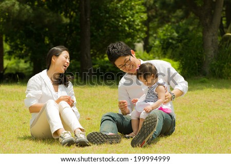 Korean family sitting in the park