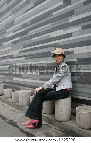 Korean girl sitting by concrete gray wall