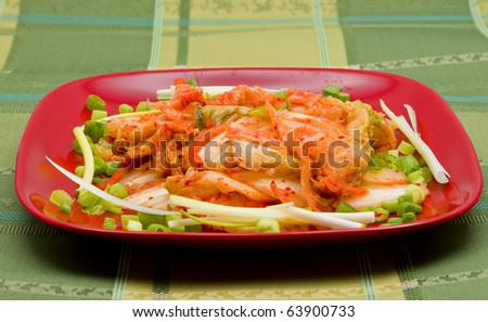 Korean kimchi (fermented cabbages) on red dish - stock photo