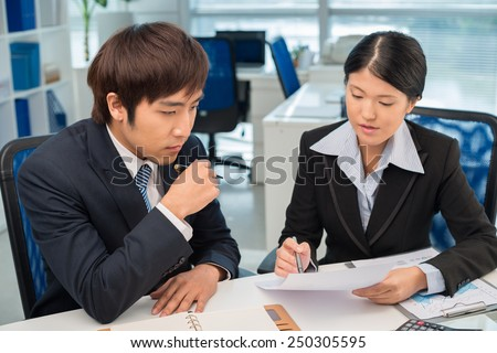 Korean manager discussing document at the meeting - stock photo
