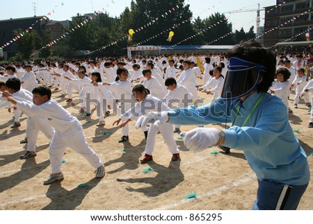 Korean school children are directed by their teacher during exercise drills