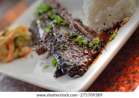 Korean short ribs on a rectangular plate with rice and kimchi in the background - stock photo