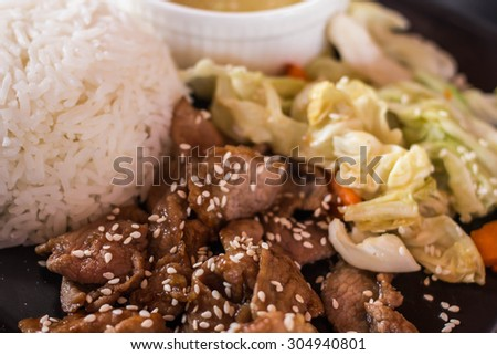 Korean style black pepper pork steak served with vegetable salad and rice, selective focus