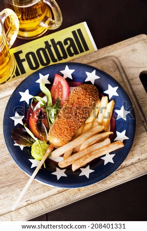 korndog with french fries on a plate in the style of Provence - stock photo