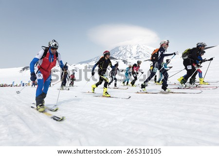 KORYAK, AVACHA VOLCANOES, KAMCHATKA, RUSSIA - APRIL 27, 2014: Mass start race, ski mountaineers climb on skis on mountain. Team Race ski mountaineering Asian, ISMF, Russian, Kamchatka Championship. - stock photo