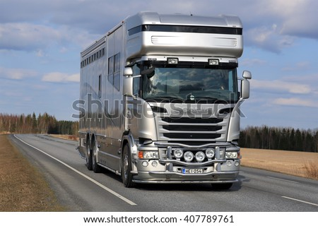 KOSKI TL, FINLAND - APRIL 16, 2016: New, modern silver Scania horsebox truck for horse transport on the road at spring.  - stock photo