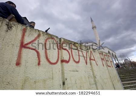 Kosova - MAY 15: Graffiti on wall on May 15, 2013, Kosova. Two unidentified boys sitting above the wall with graffiti in a city of Kosova. Kosova is a region in southeastern Europe. - stock photo