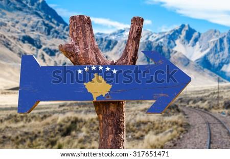 Kosovo Flag wooden sign with Railways Track background - stock photo