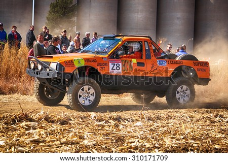 KOSTER, SOUTH AFRICA - July 11:  Africa-Offroad Racing Rally,  on July 11, 2015 at Koster, North West Province, South Africa.  HD orange truck kicking up dust on turn at rally.  - stock photo