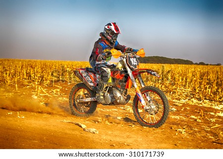 KOSTER, SOUTH AFRICA - July 11:  Africa-Offroad Racing Rally,  on July 11, 2015 at Koster, North West Province, South Africa.  HD - Motorbike kicking up trail of dust on sand track during rally race.  - stock photo