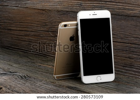 Koszalin, Poland - April 30, 2015: Photo of Golden iPhone 6 and silver iPhone 6 Plus on wooden table. iPhone 6 (4.7 inches) and 6 Plus (5.5 inches) are new generation smartphone from Apple.  - stock photo