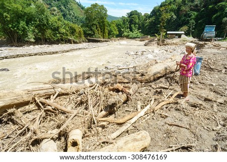 Kota Belud Sabah Malaysia-November 11, 2015:Unidentified villager looking at debris cause by mud flood at Kedamaian River after earthquake.The flood cause clean water supply interruption in this area. - stock photo