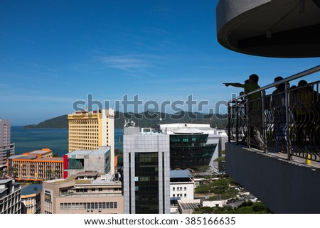 Kota Kinabalu, Malaysia - February 25, 2016: Visitors enjoying the bird's eye view of Kota Kinabalu City and the south china sea from Signal Hill Observatory Platform.