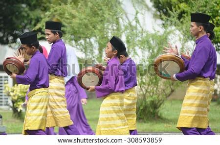 Kota Kinabalu Sabah Malaysia-December 27, 2014:Male performers dressed in Malay traditional costume playing instrument called Kompang during traditional wedding parade in Kota Kinabalu Sabah. - stock photo