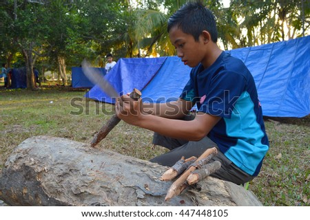 Kota Kinabalu, Sabah, Malaysia. March 29, 2016: Camper making a tent stakes from wooden sticks. Putting up sturdy tent is an essential skill during camping activities.