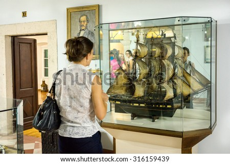 KOTOR, MONTENEGRO - SEPTEMBER 10, 2015: Maritime Museum of Montenegro. Visitor looking at the vessel model in the museum hall. - stock photo