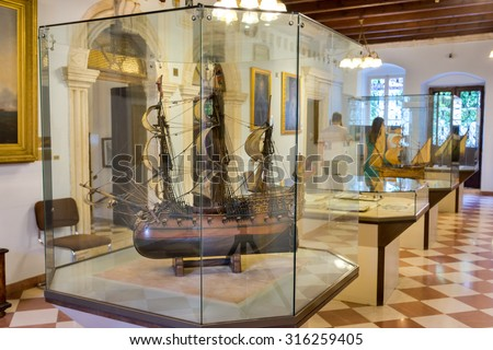KOTOR, MONTENEGRO - SEPTEMBER 10, 2015: Maritime Museum of Montenegro. Visitors looking at the exponates in the museum hall. Vessel model on the first stage, - stock photo
