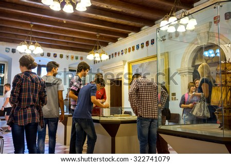 KOTOR, MONTENEGRO - SEPTEMBER 10, 2015: Maritime Museum of Montenegro. Visitors looking at the exponates in the museum hall. - stock photo
