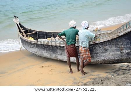 Kovalam, India â?? April  11, 2015. Fishermen near the boat on the beach of Kovalama, India. - stock photo