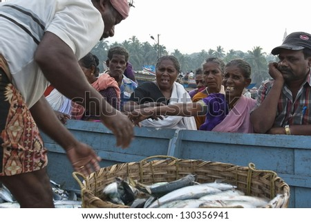 KOVALAM, INDIA - FEBRUARY 17: Unidentified Indian people bargain for a new fish catch on February 17, 2010 on Kovalam-beach in Kovalam, Kerala, India. Fishing is the main source of income for locals. - stock photo