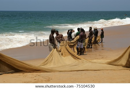 KOVALAM, INDIA - MARCH 14: Kovalam, Kerala, South India,  March 14, 2011.  Fishermen are pulling their fishing net in combined work out of the sea