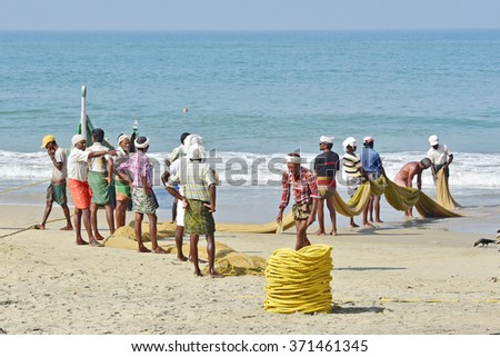 KOVALAM, KERALA, TRIVANDRUM, INDIA, FEBRUARY 03, 2016: Fishermen pulling up the net to find a disappointing harvest. A scene in the morning on the beach at Kovalam. - stock photo