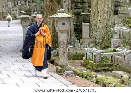 Koyasan, Japan - April 30, 2014: View of a Shingon Monk walking in Okunoin cemetery.  Koyasan is primarily known as the world headquarters of the Koyasan Shingon sect of Japanese Buddhism. - stock photo