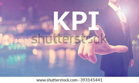 KPI concept with businessman on blurred city background