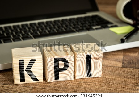 KPI (Key Performance Indicator) written on a wooden cube in front of a laptop - stock photo