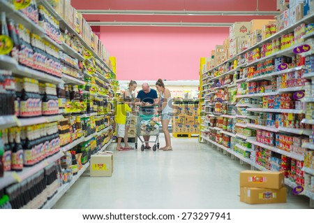 Krabi, 20 october 2014: European tourists family selects products in Tesco Lotus mall in Krabi Muang district, Krabi province, Thailand.