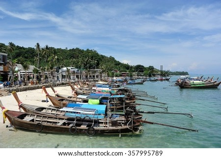 Krabi, Thailand - March 2014 : Boats parks at the white sandy beach of majestic tropical lush green Phi Phi Island with blue sky and mountain background.