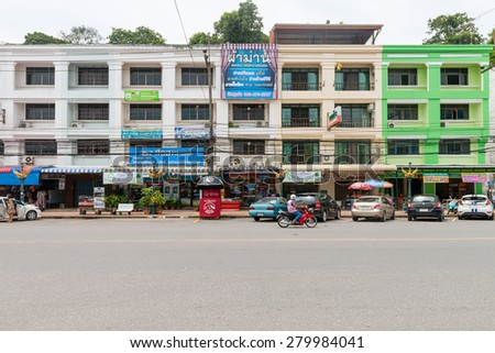 KRABI, THAILAND - 14 OCT 2014: Colorful, commercial building complex in central Krabi town, with roadside parking. - stock photo