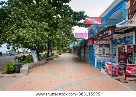 KRABI, THAILAND - 14 OCT 2014: Empty tourist street along the seaside with shops, tours agencies signs and advertising. - stock photo