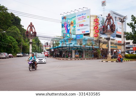 KRABI, THAILAND - 14 OCT 2014: Intersection in central Krabi Town, with giant caveman statues on high pedestals, holding traffic lights. - stock photo