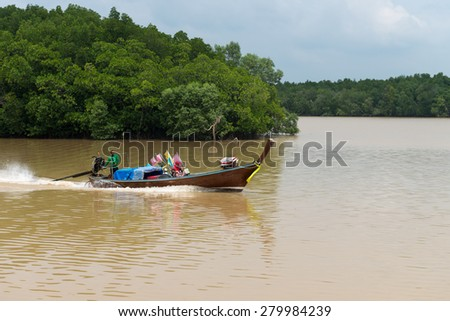 KRABI, THAILAND - 14 OCT 2014: Local fisherman and his wife, cruising along the Krabi River in Thailand in their motorized, handmade, wooden boat, with a load of nets and marker buoys. - stock photo