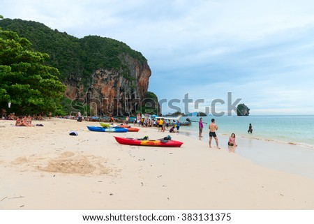KRABI, THAILAND - 12 OCT 2014: Tourists enjoying water activities and relaxing on the sand at Railay Pranang Beach Krabi.