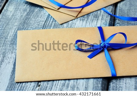 Kraft Envelope with blue ribbon tied in a bow on wooden boards. Gift  - stock photo