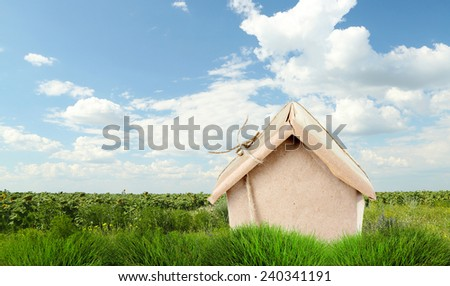 Kraft paper house on green grass in field - stock photo