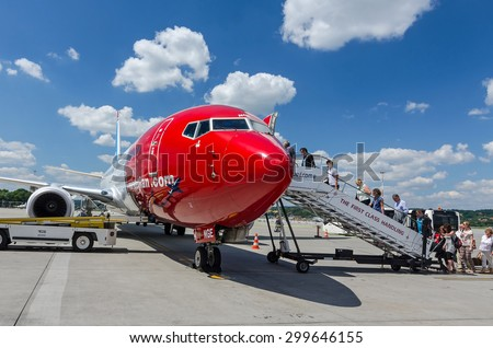KRAKOW AIRPORT, POLAND - 02 JULY 2015: People boarding to Norwegian plane on Krakow Balice Airport. Norwegian operates over 100 aircraft and is one of the biggest low-cost airline company in Europe. - stock photo