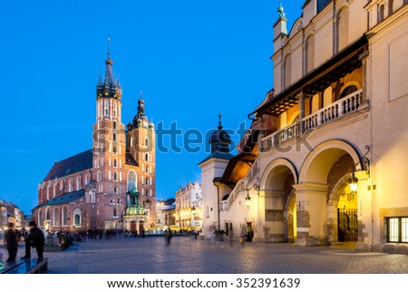 Krakow - Poland - April 22. Krakow - evening picture of old square in Krakow. People walking through the square. Highlighted Krakow Hall and Mariacki Church. Krakow - Poland - April 22, 2015 - stock photo