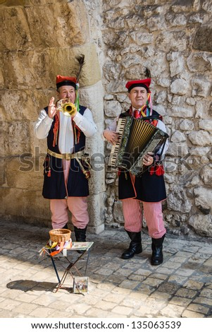 KRAKOW, POLAND - APRIL 14: Musicians in traditional folk costumes perform in the street, on April 14, 2013. Krakow is the most popular destination in Poland, full of many attractions for tourists. - stock photo