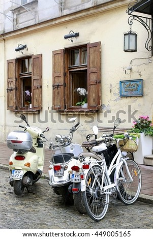 KRAKOW, POLAND - JULY 07, 2016: A bike and two vespas by the old tenement in Krakow, Poland.